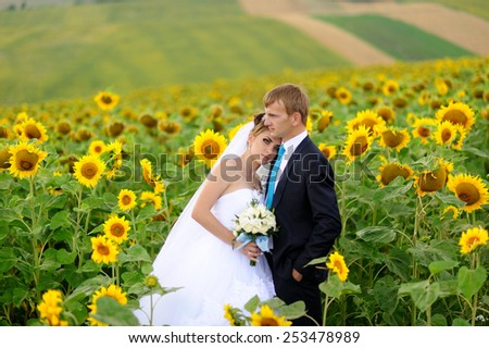 Happy bride and groom on green field with yellow sunflowers - stock photo
