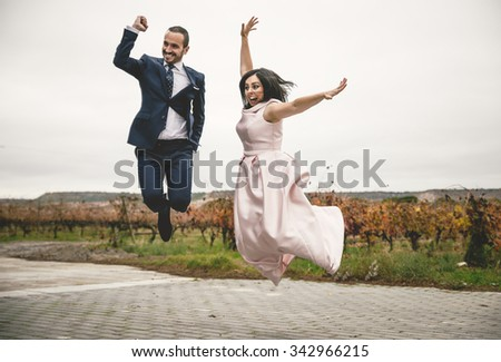 Happy bride and groom on their wedding jumping - stock photo