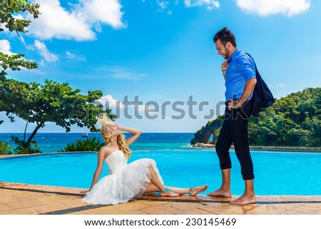 happy bride and groom poolside infinity. Tropical sea in the background. - stock photo