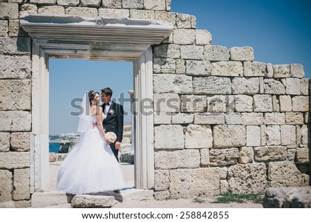 Happy bride and groom posing on the background of ancient ruins. Just married couple on the wedding  - stock photo