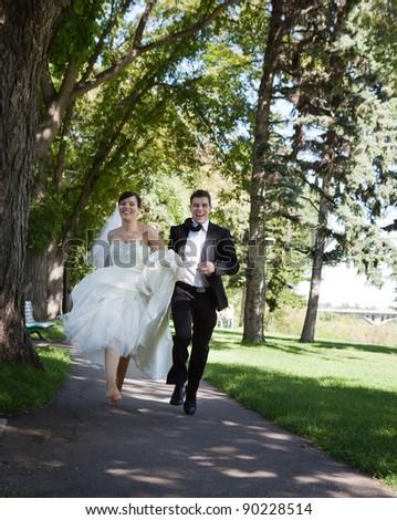 Happy bride and groom running along the walkway - stock photo