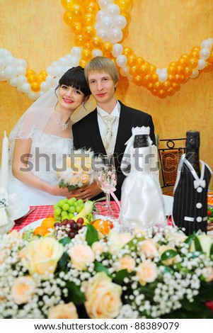 happy bride and groom sitting at banquet table and keep bouquet of roses - stock photo