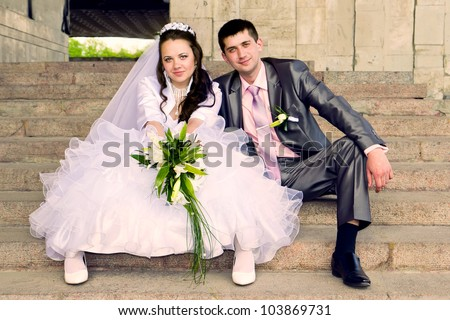 Happy bride and groom sitting on stairs outdoor