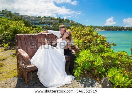 Happy bride and groom sitting on the bench in front of beautiful tropical landscape. Hotel, sea, sky, flowering plants and palm trees in the background. Wedding and honeymoon concept. - stock photo