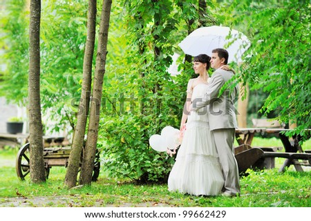 Happy bride and groom standing together in green autumn park - stock photo
