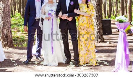 happy bride and groom standing with guests  - stock photo