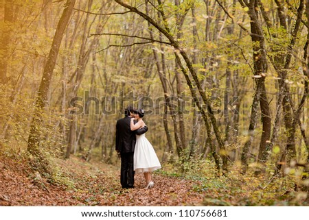 happy bride and groom walking in the autumn forest - stock photo