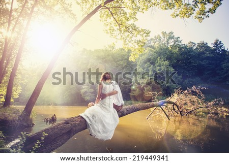 happy bride and groom walking in the forest - stock photo