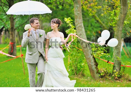 Happy bride and groom walking together in a park - stock photo
