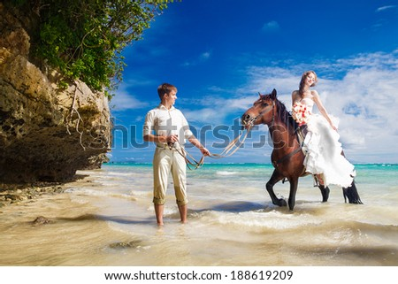 happy bride and groom walking with horse on a tropical beach - stock photo