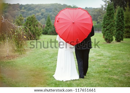 Happy bride and groom with the umbrella (soft focus, focus on umbrella) - stock photo