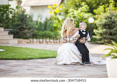 Happy bride and smiling little boy outdoors - stock photo