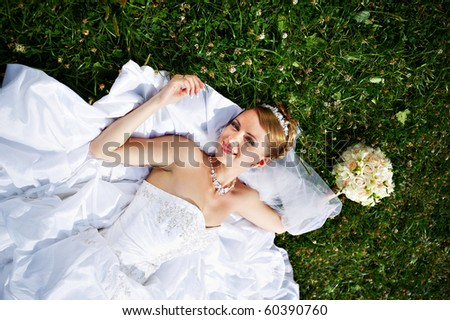 Happy bride are on grass in park - stock photo