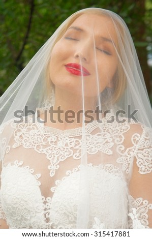 Happy bride covered with white veil - stock photo