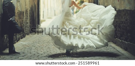 Happy bride dancing around groom. Wedding day. - stock photo