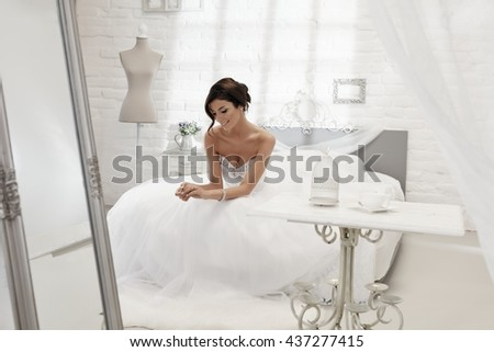 Happy bride daydreaming in bedroom, sitting on bed, looking at engagement ring. - stock photo
