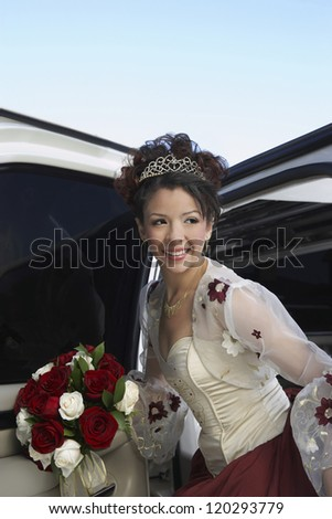 Happy  bride getting in the car with rose bouquet on wedding day - stock photo