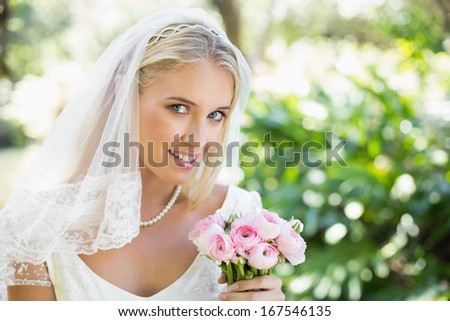 Happy bride in a veil holding her bouquet looking at camera in the countryside - stock photo