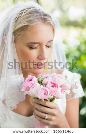 Happy bride in a veil smelling her rose bouquet in the countryside