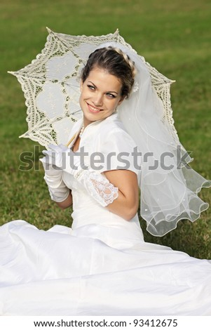 Happy bride in a white dress with a;n umbrella sitting on the lawn in the park - stock photo