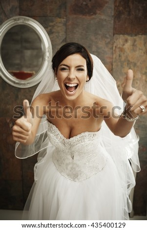 Happy bride in full glamour showing thumbs up. - stock photo