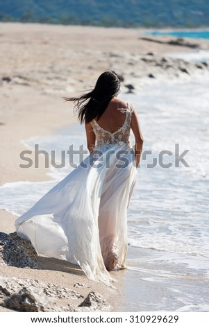 happy bride  in her snow-white dress on the beach