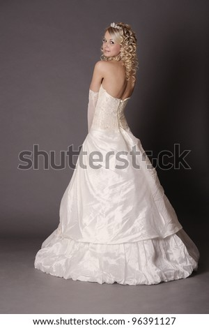Happy bride in wedding dress on a gray background, back view.