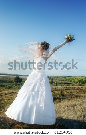 Happy bride in white dress and veil outdoors at dawn against blue sky