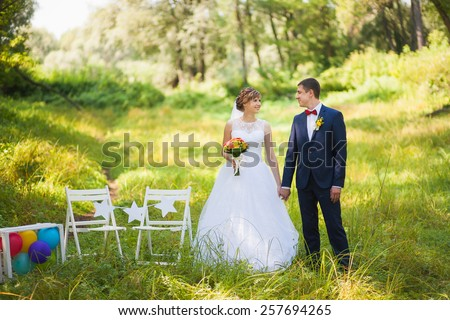 happy bride looking at  groom standing in summer green park, kissing, smiling, laughing.  wedding day. happy young couple in love. family lifestyles. beautiful people. nature background. woman man - stock photo
