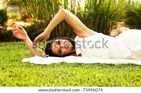 Happy bride lying on the grass, wedding day - stock photo