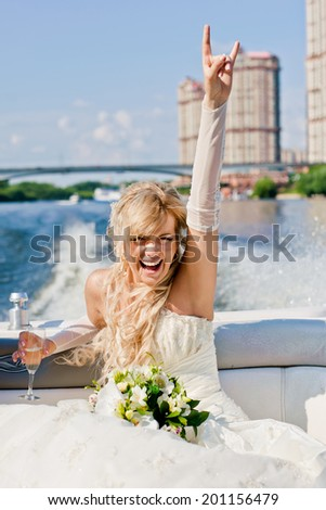 happy bride on a boat sailing with his hand raised up - stock photo