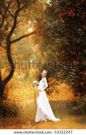 happy bride on autumn forest - stock photo