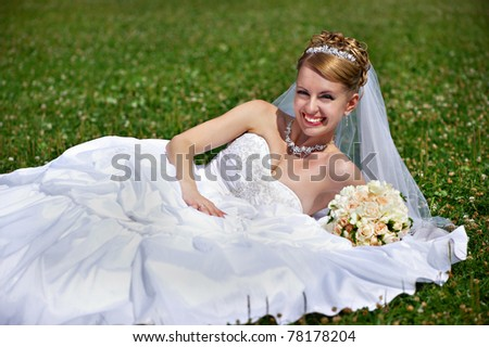 Happy bride on grass in park - stock photo