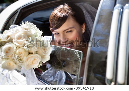Happy bride sitting in limousine holding out flower bouquet - stock photo