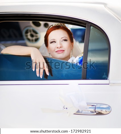 Happy bride sitting in white limo.