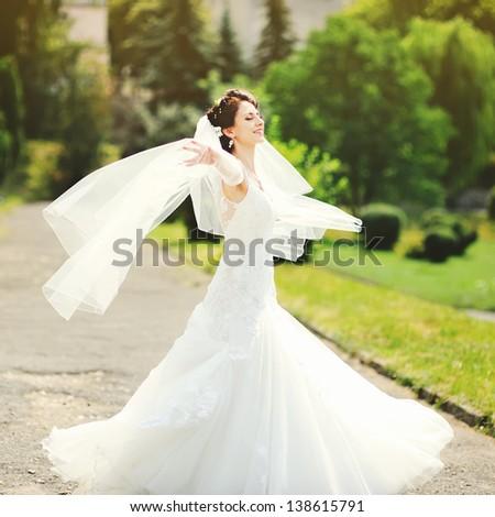 happy bride spinning around with veil - stock photo