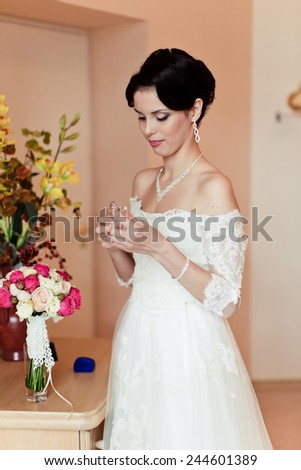 Happy Bride spraying perfume after the completion of make-up and hairstyles - stock photo