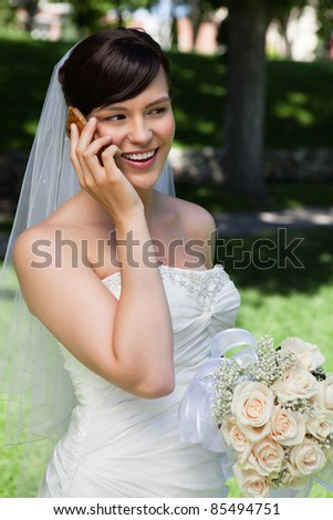 Happy bride talking over cell phone - stock photo