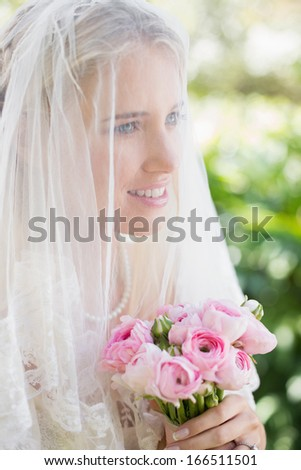Happy bride wearing veil over face holding rose bouquet in the countryside