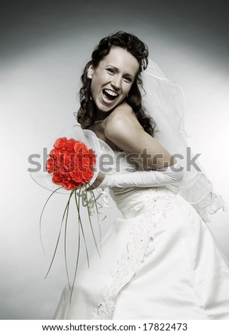 happy bride with bunch of roses over grey background - stock photo