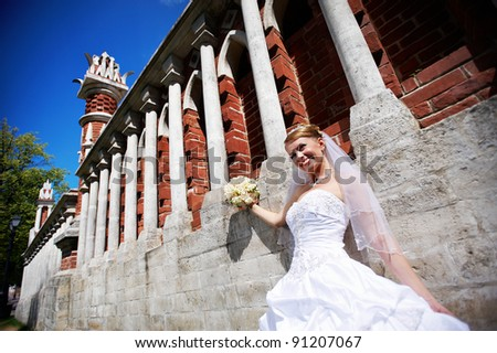 Happy Bride with flowers at wall to palace - stock photo