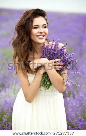 Happy bride with lavender bouquet at raining day on lavender field. Beautiful young bride in lavender field, happy woman enjoying lavender flowers. - stock photo