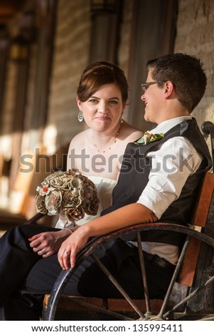 Happy bride with partner on antique bench - stock photo