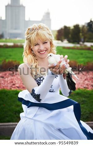 Happy bride with pigeon on the wedding walk - stock photo