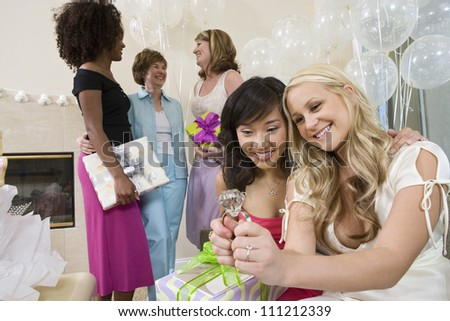 Happy bridge and friend looking at engagement ring with people standing in the background - stock photo