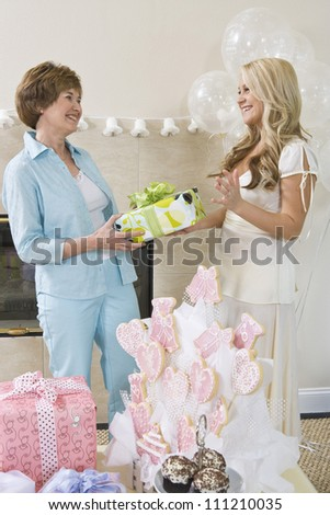 Happy bridge receiving gift from her mother at party - stock photo