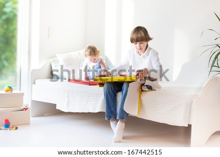 Happy brother and baby sister opening their presents on a sunny morning in a white bedroom with a big window - stock photo