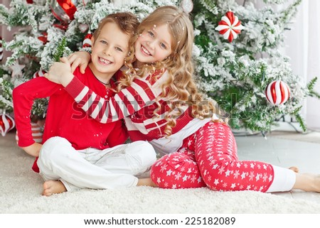 Happy brother and sister are embracing near Christmas tree. little friends enjoying New Year party, Christmastime holidays, best friends, happiness concept