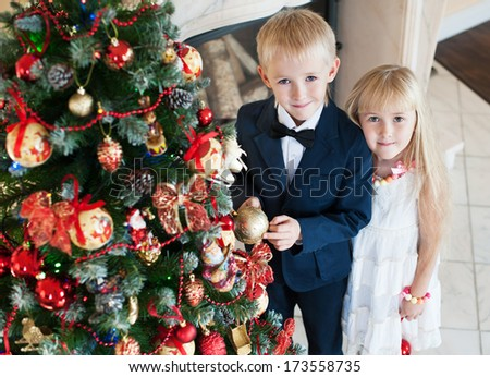 Happy brother and sister are embracing near the Christmas tree. children in evening dress on new year party  - stock photo