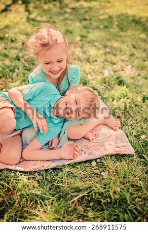 happy brother and sister are playing  in spring apple garden - stock photo